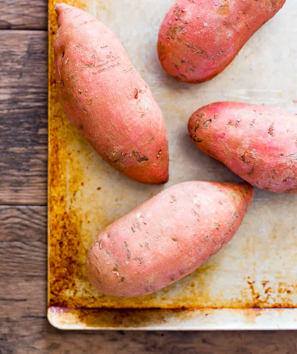 raw sweet potatoes on a sheet pan