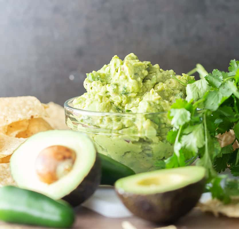 guacamole in a bowl with ingredients around it