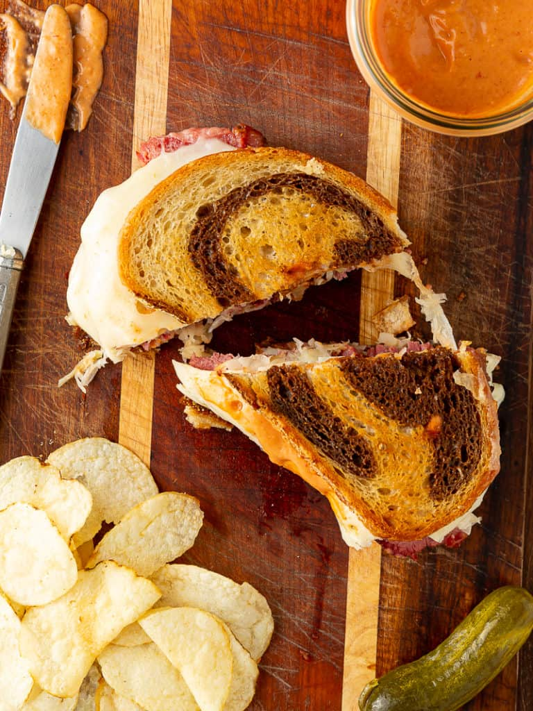 reuben sandwich with chips and pickle